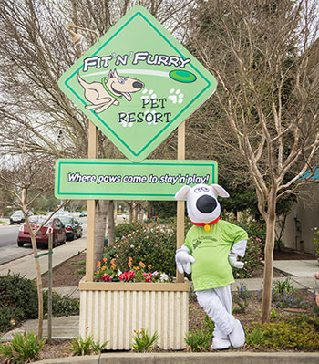Fit N Furry Mascot standing in front of our business sign